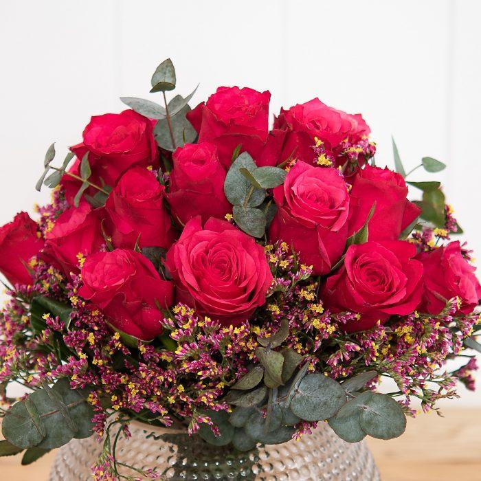 kompakt gebundener Blumenstrauß mit Strandflieder und roten Rosen