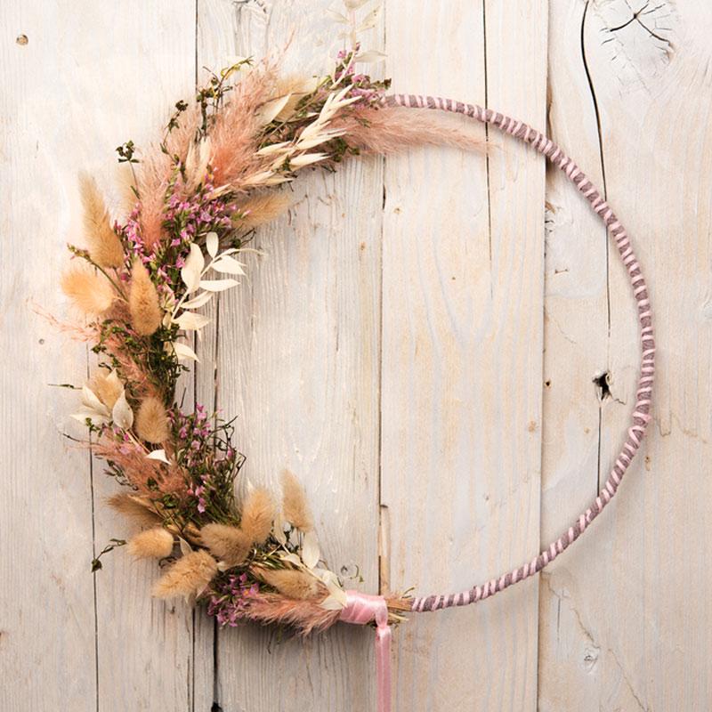 halbseitig mit Trockenblumen dekorierter Blumenring mit rosa Dekobändern
