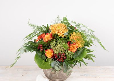 Blumen zum Geburtstag: Blumenstrauß Lotti, rund gebunden mit orangefarbenen Rosen, Chrysanthmen, Sedum in der Glaskugelvase