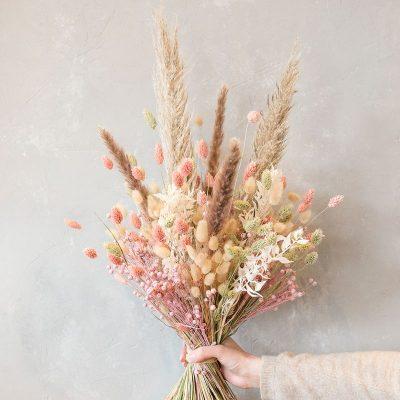 hoher, gestaffelt gebundener Trockenblumenstrauß mit rosa und naturfarbenen Gräsern, erhältlich beim Blumenversand Interfleur, Lieferung in Deutschland
