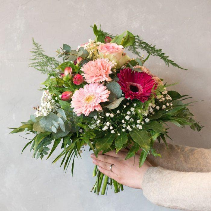 Anne: rund gebundener Blumenstrauß, liegend fotografiert, gestaltet mit rosa Gerbera, rosa Santini, rosa Inka-Lilie, pinkfarbener Gerbera, weißem Schleierkraut, Eukalyptus und frischem Blattwerk. Blumenversand, Blumenlieferung